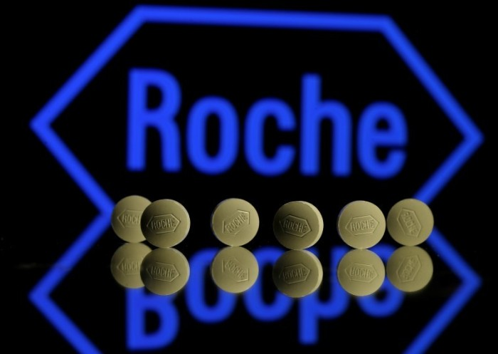 Roche tablets are seen positioned in front of a displayed Roche logo in this photo illustration shot in Zenica